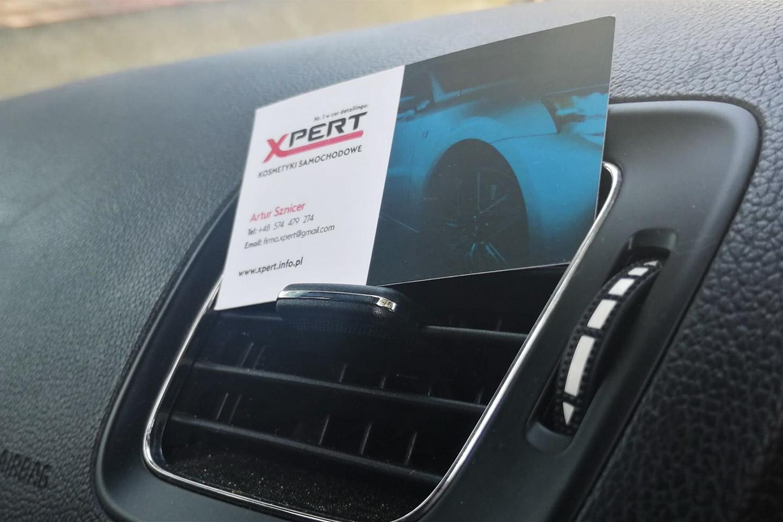 Wizytówka Xpert na kokpicie auta.